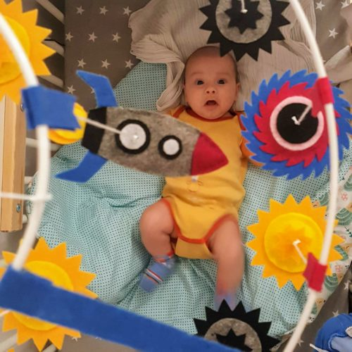 Baby Jacek with galaxy baby mobile and rocket ship