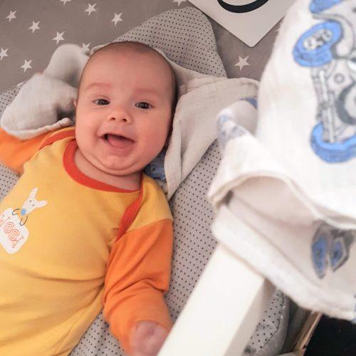 Baby Jacek smiling in a crib